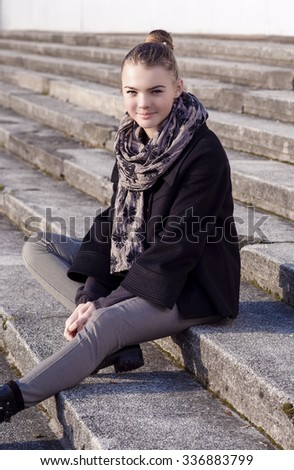 Portrait of Young Caucasian Teenager Girl Sitting On Stairs Outdoors.Vertical Image Orientation - stock photo