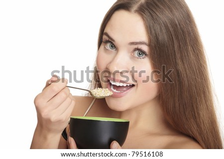 portrait of young caucasian woman eating cereals, isolated over white background. - stock photo