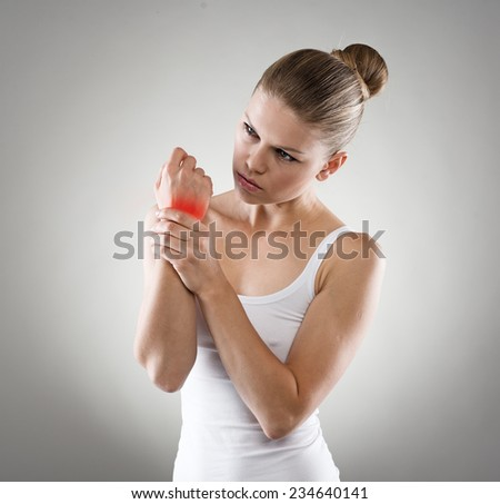 Portrait of young Caucasian woman exercising her painful wrist. Chronic osteoarthritis or joint rheumatism. Medical treatment and health care concept.  - stock photo
