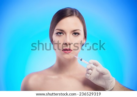 Portrait of young Caucasian woman getting cosmetic injection - stock photo