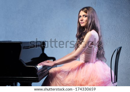 Portrait of young caucasian woman in fluffy dress sitting at the grand piano - stock photo