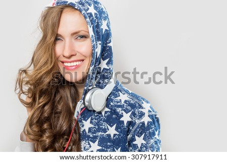 Portrait of young caucasian woman with curly long hair and headphones - stock photo