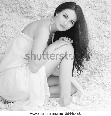 Portrait of young charming brunette woman wearing white dress sitting in sawdust.
