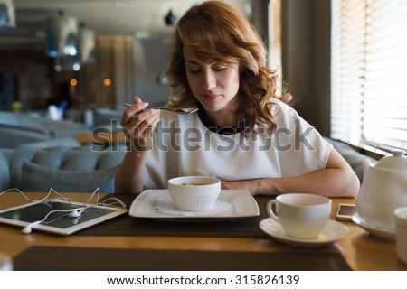 Portrait of young charming female drinking tea and tastes yummy caramel dessert while enjoying her recreation time in modern coffee shop, nice woman breakfast in cafe after work on her digital tablet - stock photo