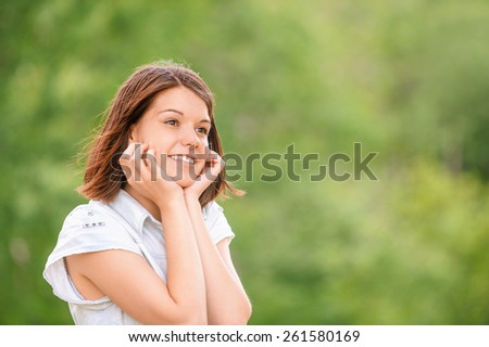 Portrait of young charming sad brunette woman at summer green park - stock photo