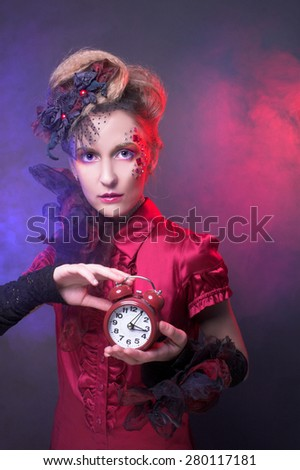 Portrait of young charming woman in artistic image posing with clock - stock photo
