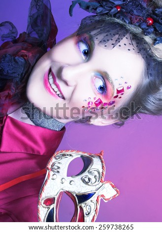 Portrait of young charming woman in artistic image posing with mask