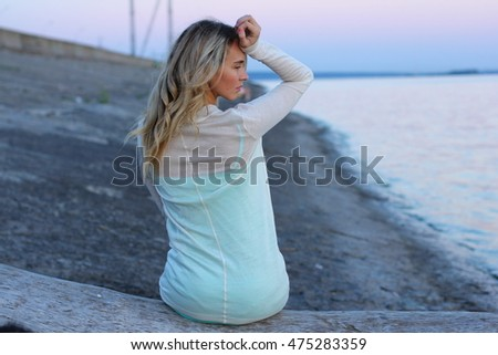 Portrait of young charming woman in blue dress relaxing while sitting near ocean in summer evening, attractive carefree female during recreation time in weekend.