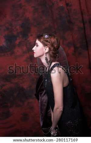 Portrait of young charming woman in ethnic image posing near cage. - stock photo