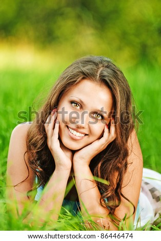 Portrait of young charming woman propping up her face, lying on grass at summer green park. - stock photo