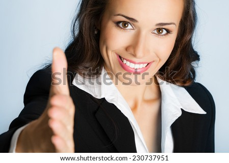 Portrait of young cheerful beautiful business woman giving hand for handshake, over blue background - stock photo