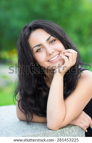 Portrait of young cheerful brunette posing near stone fence - stock photo