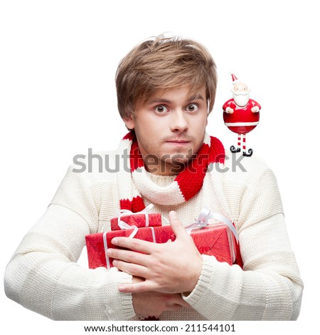 portrait of young cheerful caucasian man which holding many red christmas gifts and looking at small santa on his shoulder - stock photo