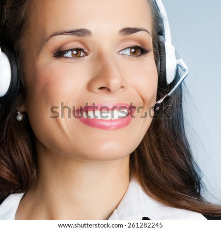 Portrait of young cheerful customer support phone operator in headset, against blue background - stock photo