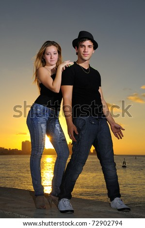 Portrait of young cheerful hispanic couple standing at sunset - stock photo
