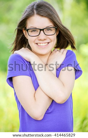 Portrait of young cheerful laughing woman wearing purple blouse and eyeglasses standing at summer green park. - stock photo