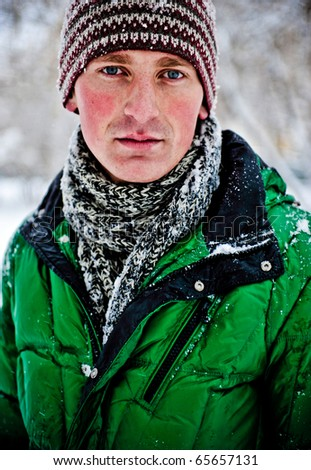 Portrait of young cheerful man outdoor in winter park - stock photo
