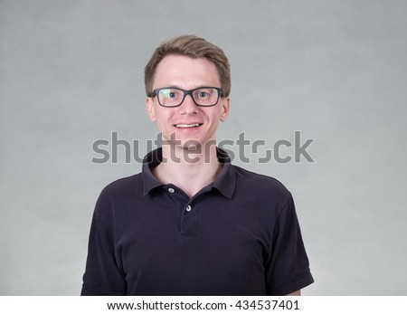 Portrait of young cheerful man with glasses on grey background