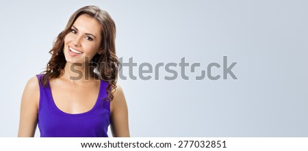 Portrait of young cheerful smiling woman in violet smart casual clothing, against grey background, with blank copyspace area for slogan or text - stock photo