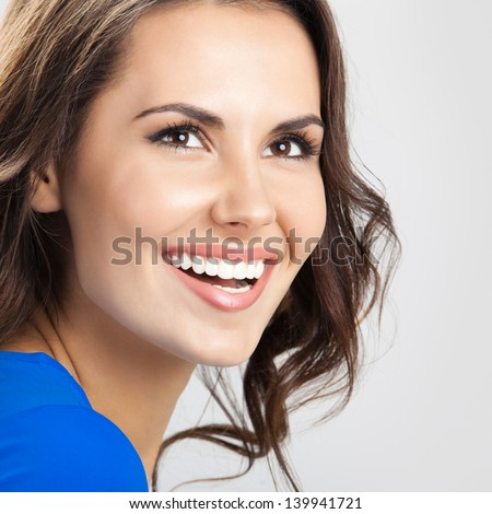 Portrait of young cheerful smiling woman, over grey background - stock photo