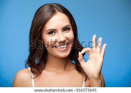 Portrait of young cheerful smiling woman showing okay gesture, over blue background - stock photo