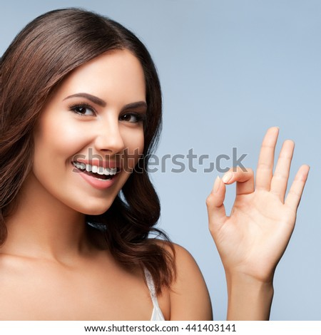 Portrait of young cheerful smiling woman showing okay gesture, over grey background - stock photo