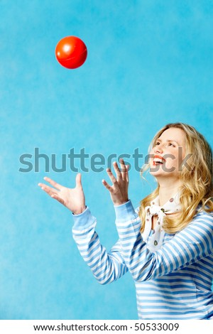 Portrait of young cheerful woman playing with a ball - stock photo