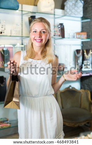 portrait of young cheerful woman standing among showcases in bijouterie boutique