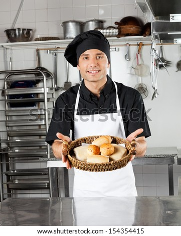 Portrait of young chef holding basket of breads in restaurant kitchen
