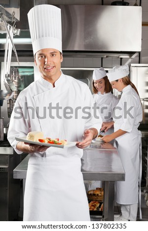 Portrait of young chef presenting dish with colleagues standing in background at commercial kitchen - stock photo