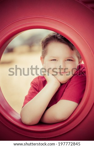 Portrait of young child playing on playground in image with vintage filter effect - stock photo