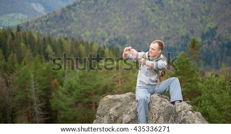 Portrait of young climber sitting on the peak of rock makes the photo on the his phone on the blurred background of forest valley