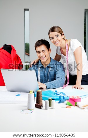 Portrait of young clothing designers working on laptop together in workshop