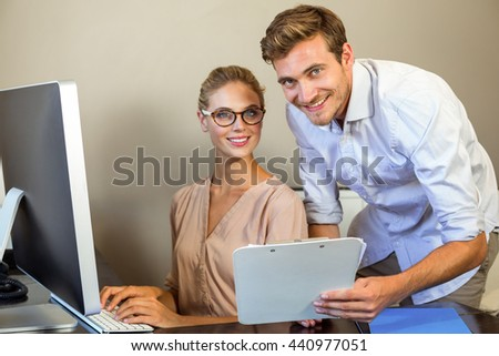 Portrait of young colleagues with documents at desk in office - stock photo