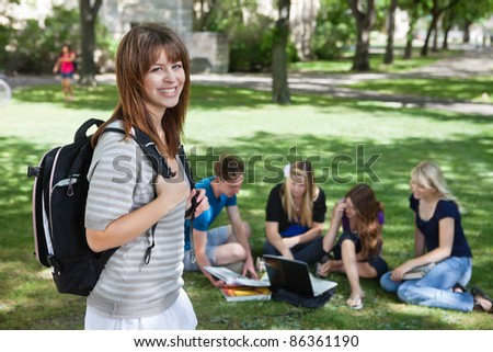 Portrait of young college girl at college campus with classmates studying in background - stock photo