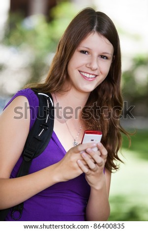 Portrait of young college girl holding cell phone
