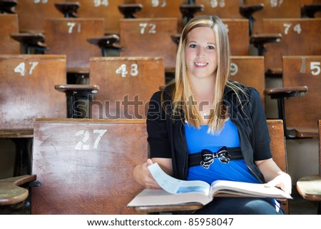 Portrait of young college girl studying at university hall - stock photo