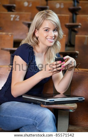 Portrait of young college girl using cell phone - stock photo