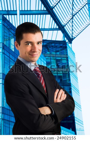 Portrait of young confident businessman against new modern blue office building - stock photo