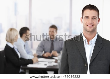 Portrait of young confident businessman in meeting room, with colleagues in background.? - stock photo