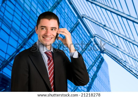 Portrait of young confident businessman talking on mobile phone outside the office - stock photo
