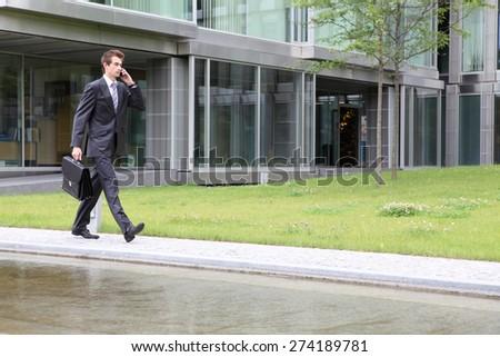 portrait of young confident caucasian businessman talking on cellphone - stock photo