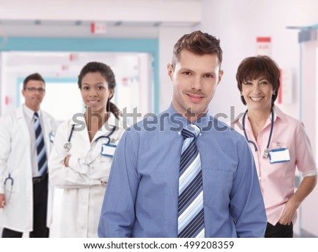 Portrait of young confident hospital manager with medical team. Smiling, standing, looking at camera, wearing tie.