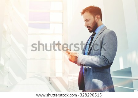 Portrait of young confident man economist holding digital tablet while standing in modern office corridor, male managing director dressed in luxury corporate clothes working on touch pad during break  - stock photo
