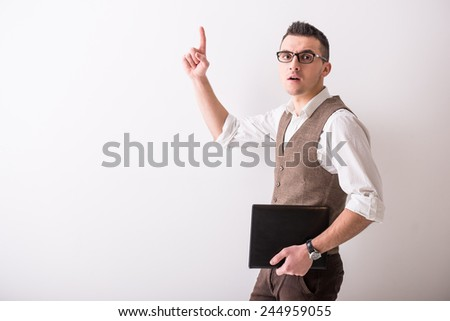 Portrait of  young confident man with tablet on grey background. - stock photo