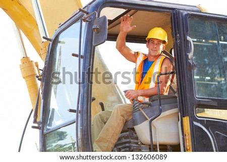 Portrait of young construction worker driving forklift waving.