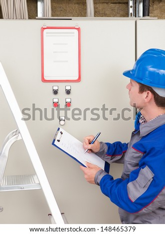 Portrait of young construction worker writing on clipboard - stock photo
