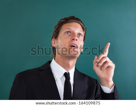 Portrait Of Young Contemplated Businessman Looking Up - stock photo
