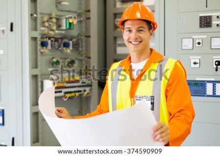 portrait of young control room engineer holding blueprint - stock photo