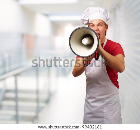 portrait of young cook man screaming with megaphone at entrance of modern building